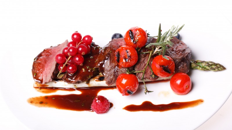 Medallions of pork, meat, asparagus, raspberries, red currant sauce, cherry tomatoes (horizontal)