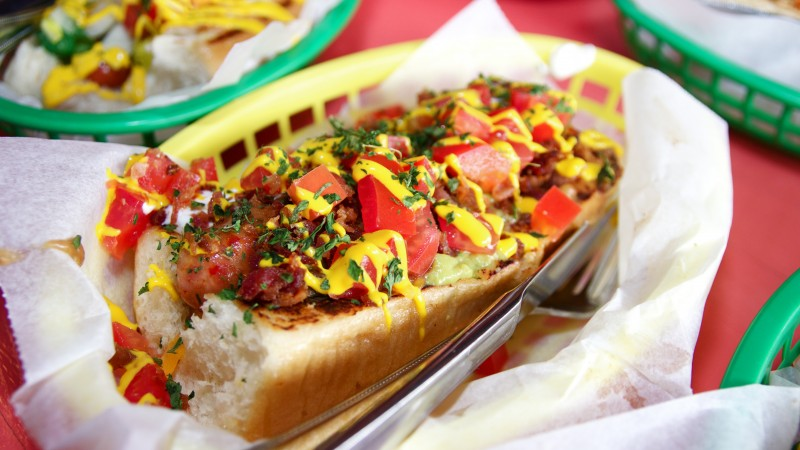 dat dog, hot dog, ketchup, mustard, lettuce, tomatoes, peppers, cucumbers (horizontal)