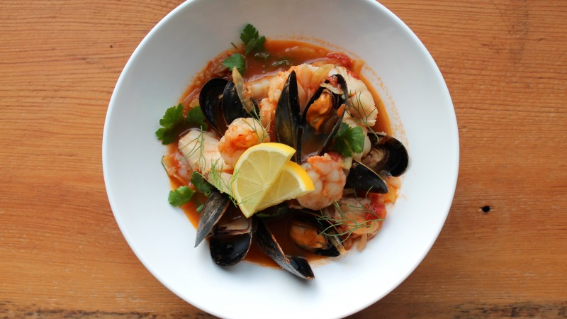 seafood soup, tomatoes, mussels, shrimp, greens (horizontal)