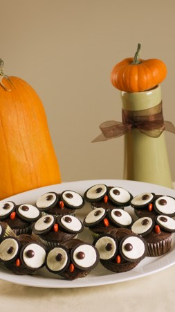 Halloween, All Hallows' Eve, All Saints' Eve, holiday table, candy, muffins, apple, pumpkin (vertical)