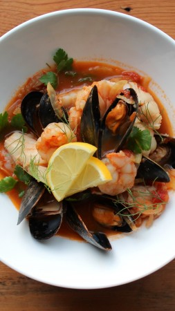 seafood soup, tomatoes, mussels, shrimp, greens (vertical)